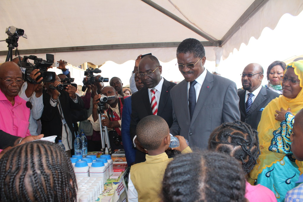 Minister of Public Health deworming a school boy